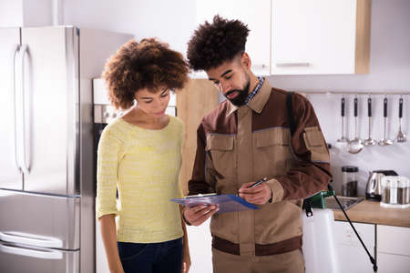 Young Male Pest Control Worker Showing Invoice To Woman In Domestic Kitchen Archivio Fotografico
