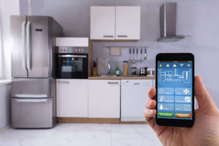 Close-up Of A Persons Hand Using Smart Home System On Mobilephone In Kitchen