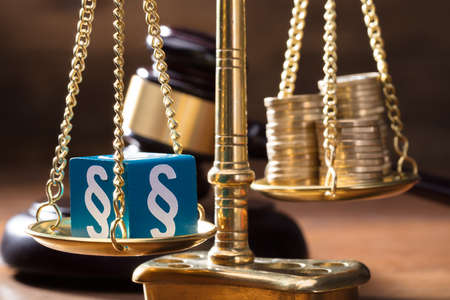 Close-up Of Blue Paragraph Block Balancing With Coins Stack On The Golden Scale Of Justice Фото со стока