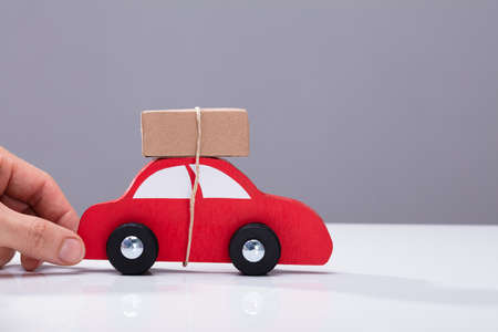 Human Hand Holding Red Car With Cardboard Box Against Grey Background