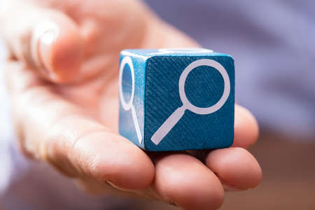 Close-up Of A Persons Hand Holding Wooden Block With Magnifying Glass Symbol On It Фото со стока