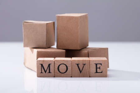 Close-up Of Move Text On Wooden Blocks In Front Of Cardboard Boxes Фото со стока