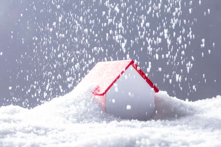 Close-up Of Snow Falling On House With Red Roof In Winter