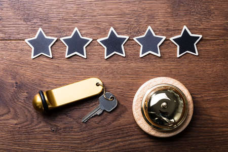 High Angle View Of Black Five Stars, Service Bell And Hotel Key On Wooden Desk Фото со стока
