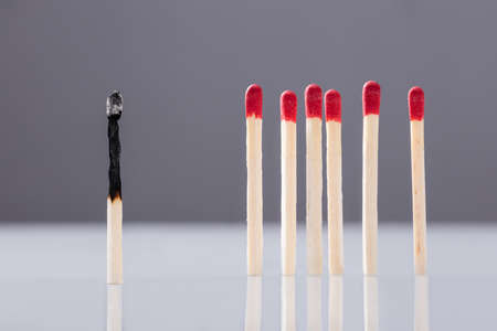 Burnt Matchstick Separated By Red Matchsticks Against Grey Background