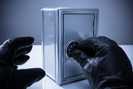 Close-up Of A Thiefs Hand Wearing Gloves Unlocking Safe