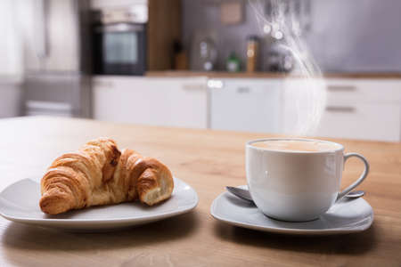 Croissant And Cup Of Hot Coffee On Wooden Desk At Breakfast