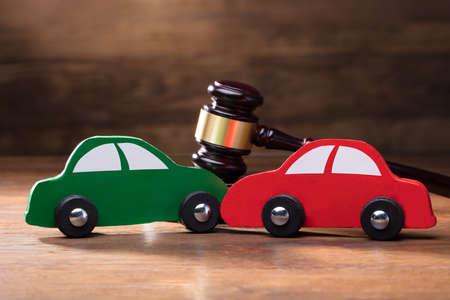 Zderzenie dwóch drewnianych samochodów zabawek przed młotkiem na drewnianym stole