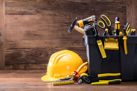Close-up Of Safety Helmet With Tools In The Black Container On The Wooden Table Stock Photo