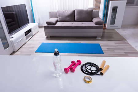 Elevated View Of Skipping Rope With Pink Dumbbells And Measurement Tape On White Desk Фото со стока