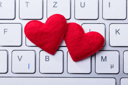 Elevated View Of Soft Two Red Hearts Shape On Keyboard