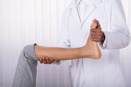 Physiotherapist's Hand Giving Leg Exercise To Female Patient In Clinic