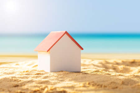 Close-up Of A House Model With Red Roof On Sandy Beach Фото со стока