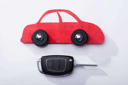 Close-up Of Red Car And Key On White Background
