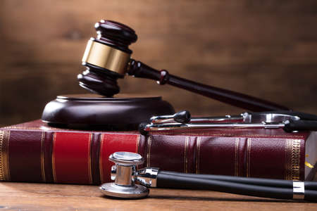 Close-up Of Judge Gavel And Soundboard On Law Book With Stethoscope Over The Wooden Desk Фото со стока