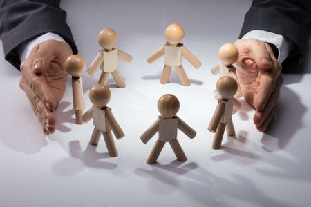 Human Hand Protecting Wooden Figures On White Background
