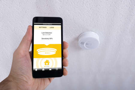 Close-up Of A Human Hand Holding Mobile Phone In Front Of Smoke Detector On Ceiling Фото со стока