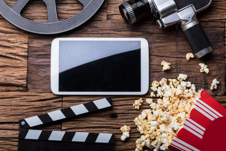 Elevated View Of Smartphone And Spilled Popcorn With Film Equipment