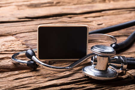 Close-up Of Blank Slate And Stethoscope On Wooden Background Фото со стока