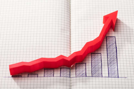Elevated View Of Red Arrow Over Increasing Graph On Chequered Notebook