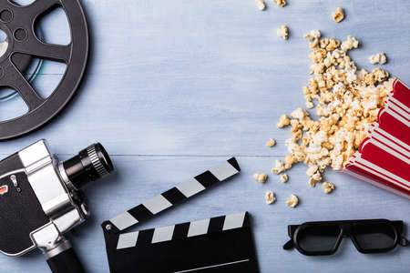 High Angle View Of Spilled Popcorn With Clapperboard, 3d Glasses, Film Reel And Movie Camera