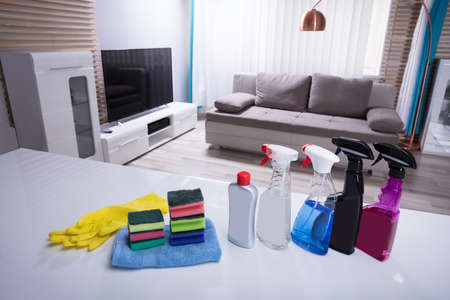 Different Cleaning Spray Bottles With Sponge And Gloves On White Desk