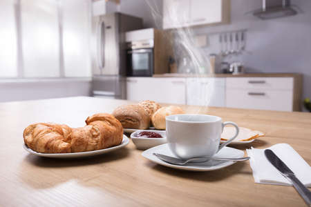 Close-up Of Croissants And Cup Of Hot Coffee On Wooden Desk