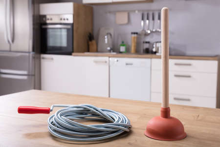 Close-up Of Plunger And Plumbing Tool On Wooden Desk