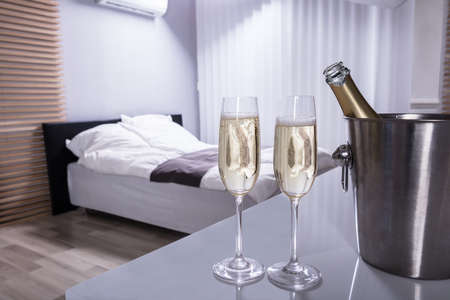 Close-up Of Two Champagne Glasses On Table In Bedroom