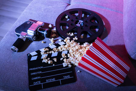 High Angle View Of Spilled Popcorn With Clapperboard And Movie Camera At Night
