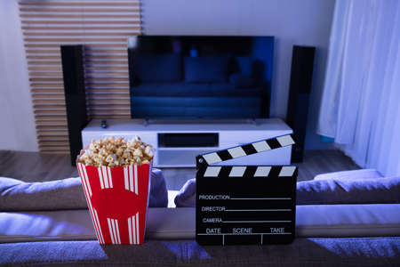 Close-up Of Clapperboard And Popcorn In Front Of Television