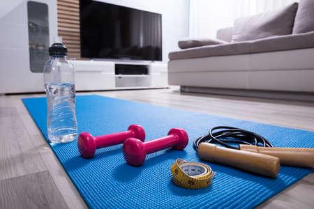 Skipping Rope With Pink Dumbbells And Measurement Tape On Fitness Mat