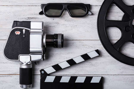 Elevated View Of Movie Camera, 3d Glasses, Film Reel And Clapper Board On Wooden Plank