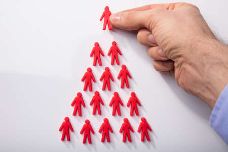 Close-up Of A Persons Hand Arranging Red Human Figures In Triangular Shape On White Background Stock Photo