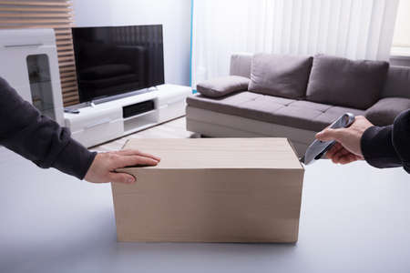 Persons Hand Opening Cardboard Box With Sharp Cutter Knife Фото со стока