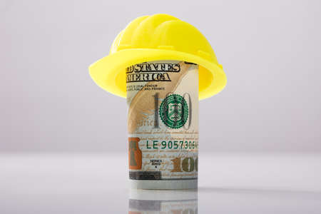 Close-up Of Yellow Hard Hat Over Rolled Up American Banknote On White Background Фото со стока
