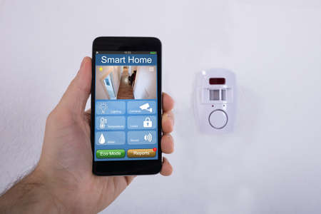 Human Hand Using Mobile Phone In Front Of Security System Mounted On Wall Фото со стока