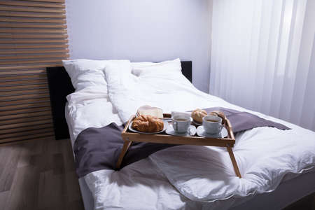 Fresh Croissants And Cup Of Tea On Bed At Breakfast
