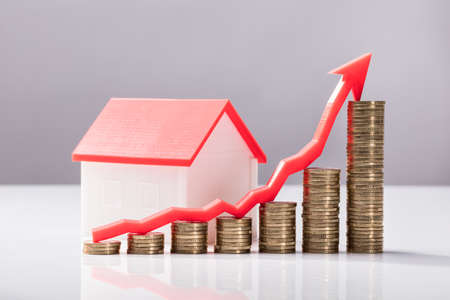 Close-up Of Increasing Graph Of Coins And House Model On White Desk