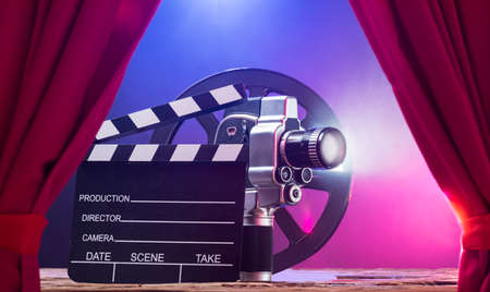Illuminated Movie Camera With Clapperboard And Film Reel Against Colored Background Фото со стока