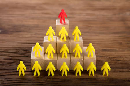 Red Figure Standing On Top Of Yellow Human Figures Over Wooden Blocks