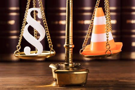 Close-up Of White Paragraph Symbol And Traffic Cone On Justice Scale In Courtroom