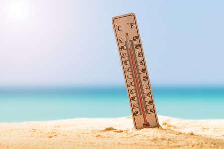 Close-up Of Thermometer On Sand Showing High Temperature Фото со стока