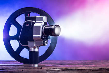 Close-up Of An Illuminated Movie Camera And Film Reel On Wooden Desk