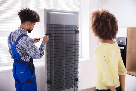 Woman Looking At Technician Repairing Refrigerator With Screwdriver In Kitchen Reklamní fotografie