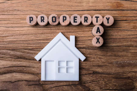 Elevated View Of House Model Near Blocks With Property And Tax Text On Wooden Background