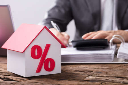 Nahaufnahme eines Hausmodells mit Prozent Symbol und rotem Dach auf hölzernem Schreibtisch Standard-Bild