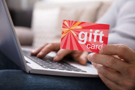 Close-up Of A Human Hand Holding Gift Card While Using Laptop