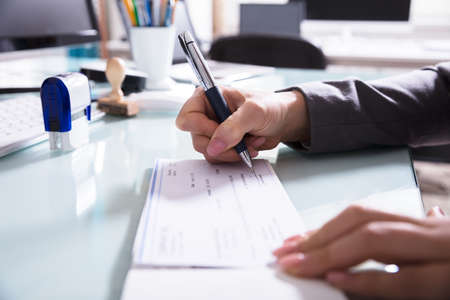 Close-up Of A Businesspersons Hand Signing Cheque With Pen In Office