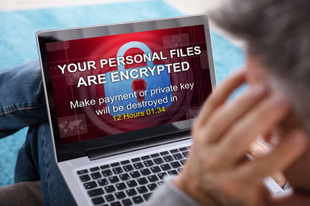Close-up Of A Person Looking At Laptop Screen Showing Personal Files Encrypted Text